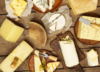 Various types of cheese on rustic background stock vector