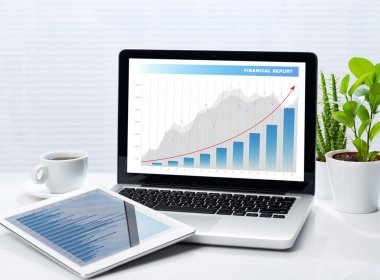 Financial graphs on laptop and tablet