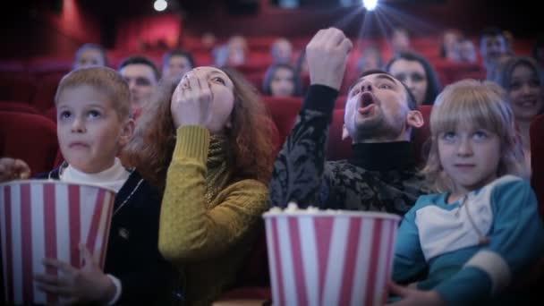 Emberek pattogatott kukoricát eszik, és grimaszok moziban