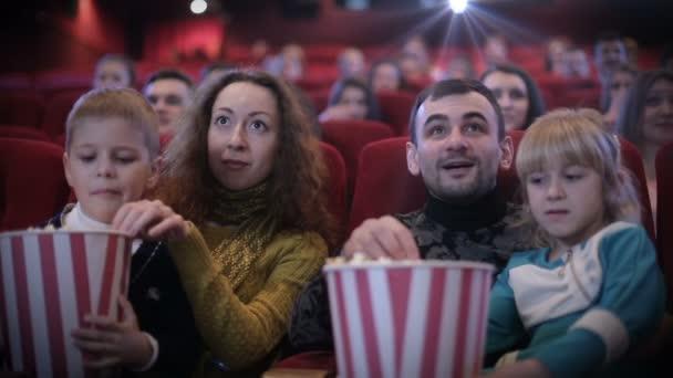 Familie isst Popcorn im Kino