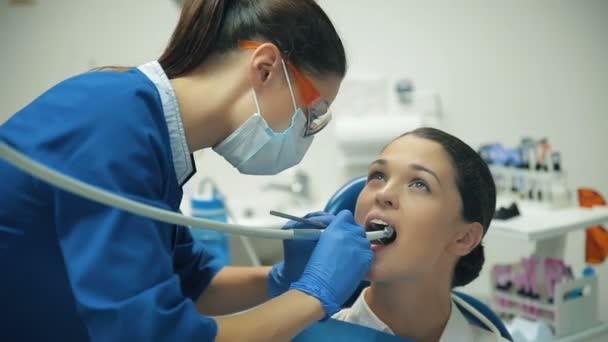 Frau behandelt Zähne beim Zahnarzt