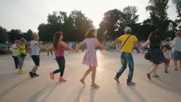 Menschen tanzen in einem Kreis, Hand in Hand