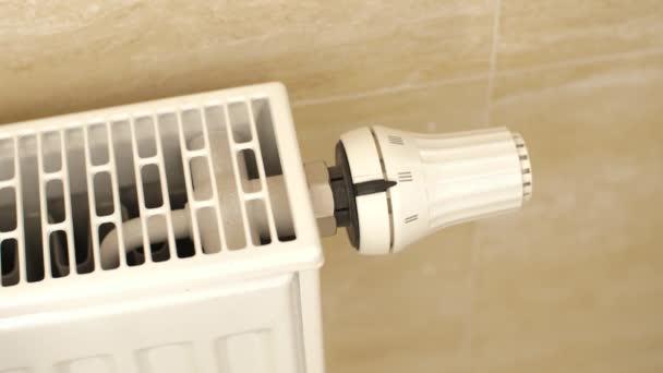 Mann dreht Thermostat einer Heizung