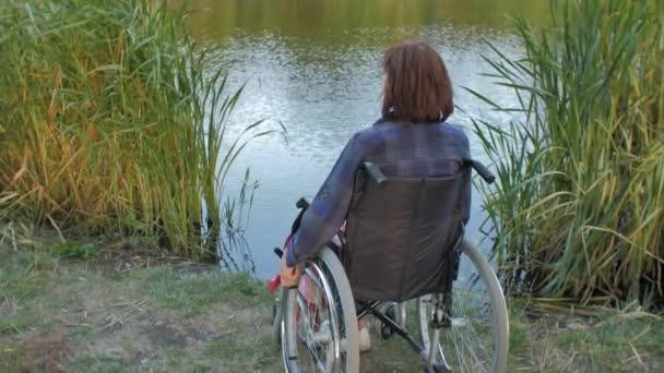 Ältere Frau sitzt im Rollstuhl am See
