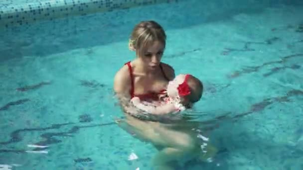 Mother with her baby in the pool