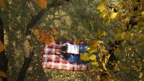 Pár ležící pod podzimní strom
