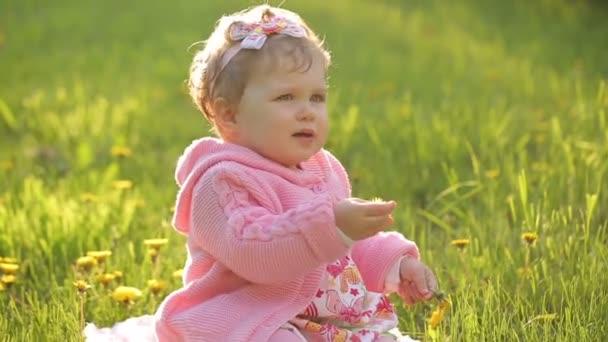 Dítě sedí na zelené trávě