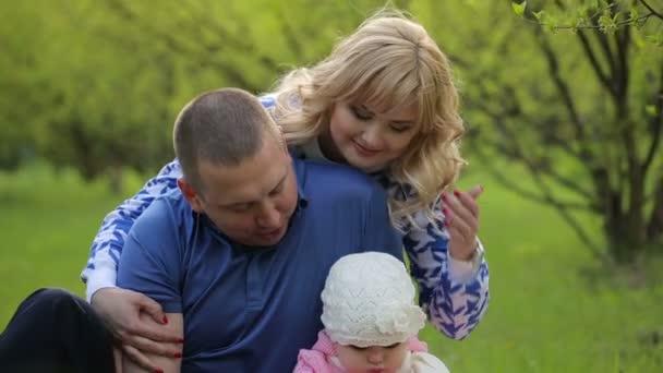 Šťastná rodina sedět na trávě v přírodě
