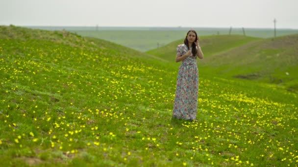 Žena v dlouhých šatech na louce