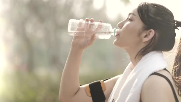 Woman drinking water from bottle after working out, outdoor sport brunette girl drink clear mineral water after training