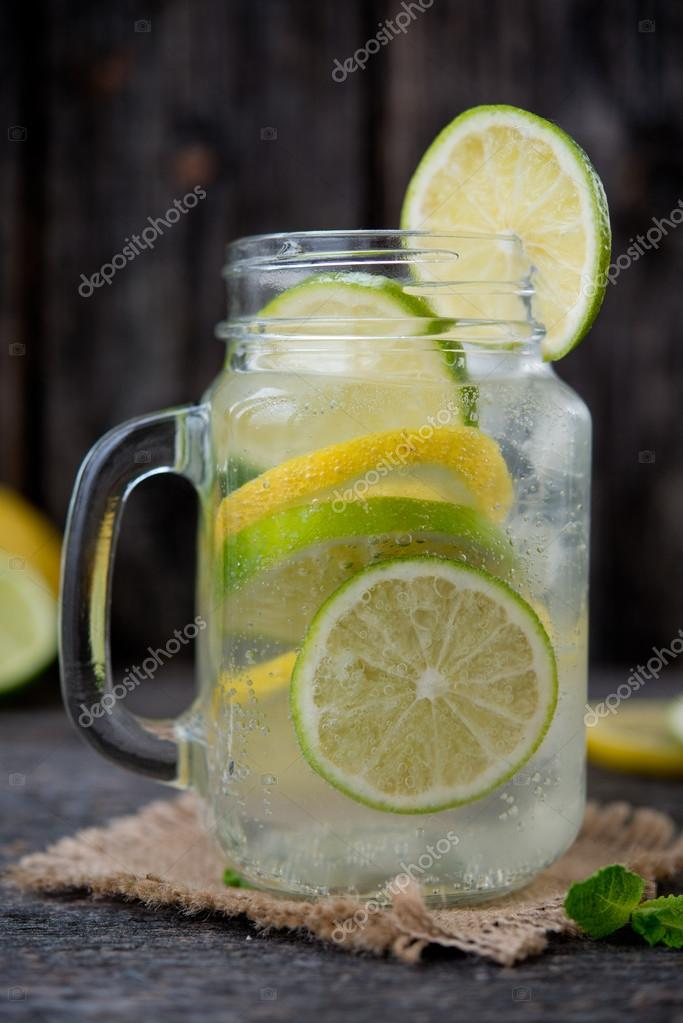 Mineral water with a fresh lemon, a lime and mint. Detox water ...