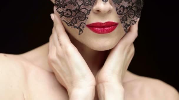Udržujte tajemství pro mě. Detailní záběr sexy tajemné červené rty ženy nosit karneval maska provádění gest sykavých fotoaparátu na černém pozadí