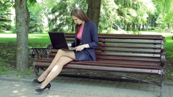 Mladé ženy s notebookem pracovat lavičce v parku