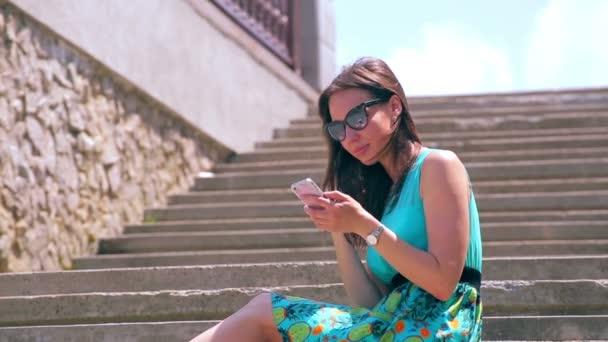 Atraktivní dívka surfování Internet po telefonu sedět na starých schodech. Zavřít