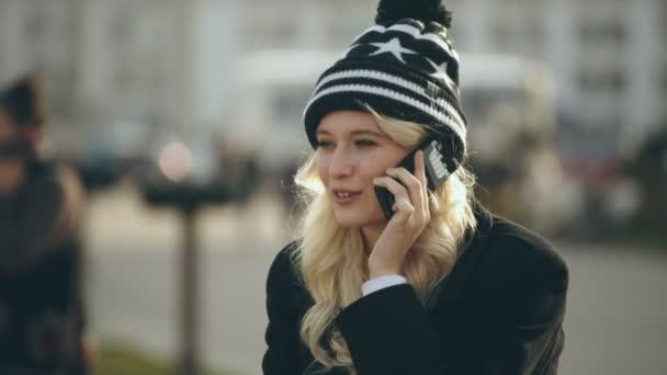 blonde junge Frau telefoniert mit dem Handy und lächelt 2