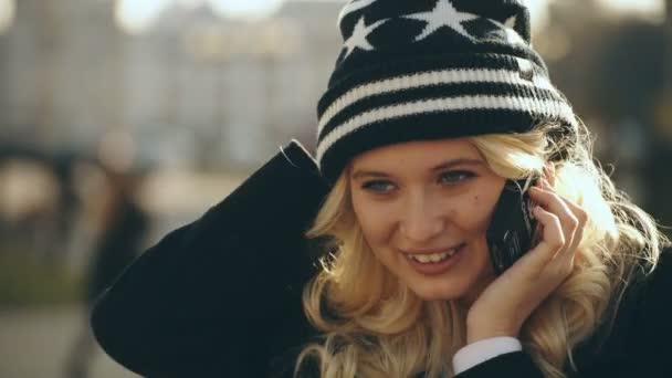 blonde junge Frau telefoniert mit dem Handy und lächelt 4