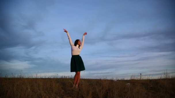 A young woman is dancing against the evening sky