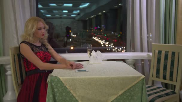 Krásná blondýna mladá žena v restauraci café čeká na někoho