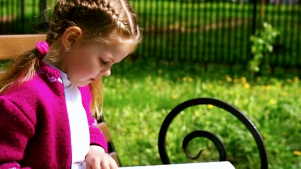 Dívka čtoucí knihu zatímco sedí na lavičce