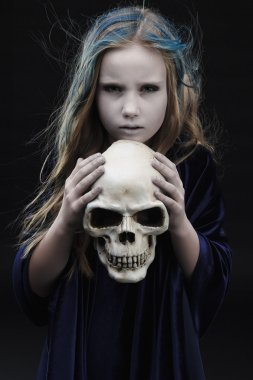 Little girl in halloween costume of the witch with the bone