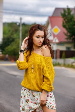 High fashion stylish hipster girl in the yellow sweater outdoor