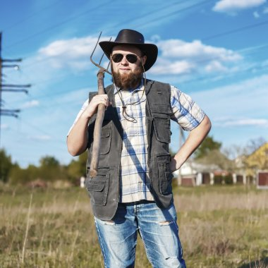 Farmer in the hat and sunglasses with the pitchfork outdoor