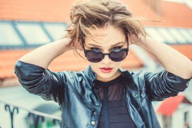 Stylish girl in the leather jacket and sunglasses outdoor portrait