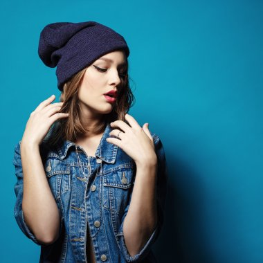 Closeup studio shot of pretty hipster teenage girl with beanie hat wearing jeans jacket looking at camera posing.