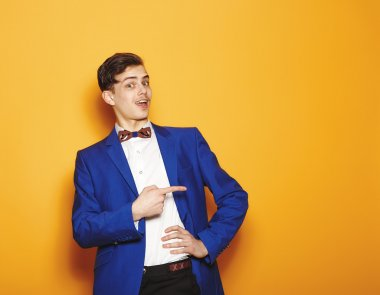 Portrait of young handsome business man,  over yellow background