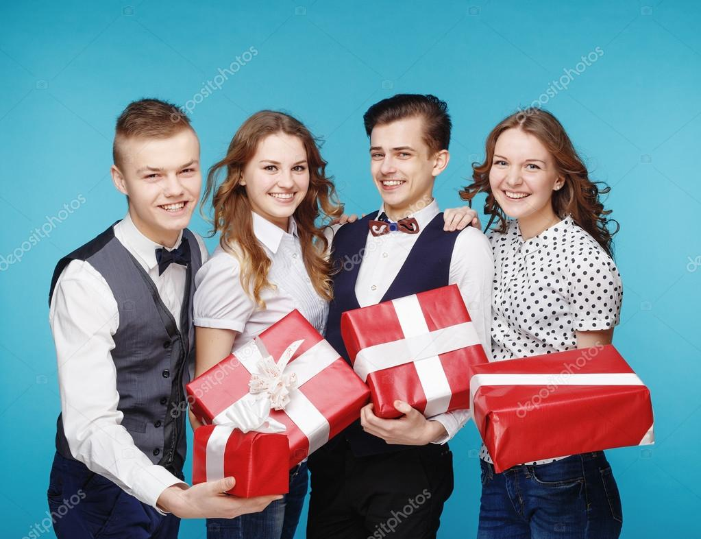 Students holding red gift boxes. Female and male model studio posing. Hipster Style