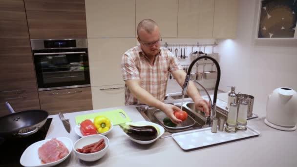 Ein Mann, waschen das Gemüse in der Küchenspüle