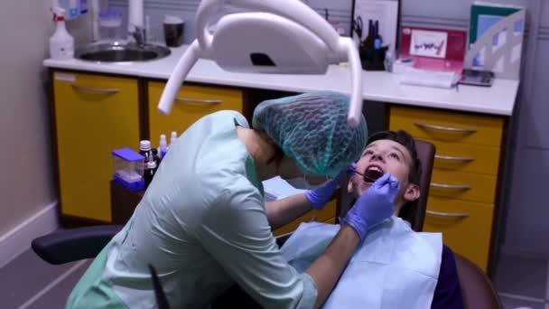The dentist examines the teeth teenager