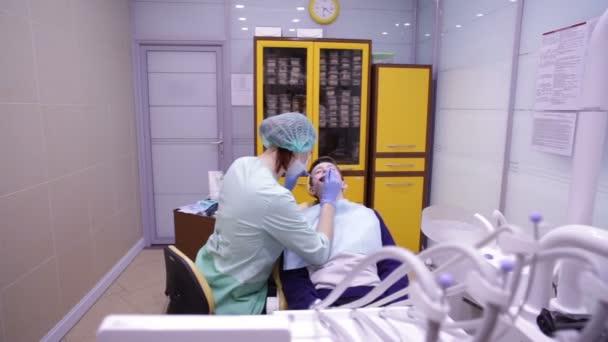 Stomatologie. Lékař zkoumá zuby teenager