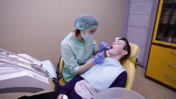 Lékař zkoumá chlapci zuby zubní křesla
