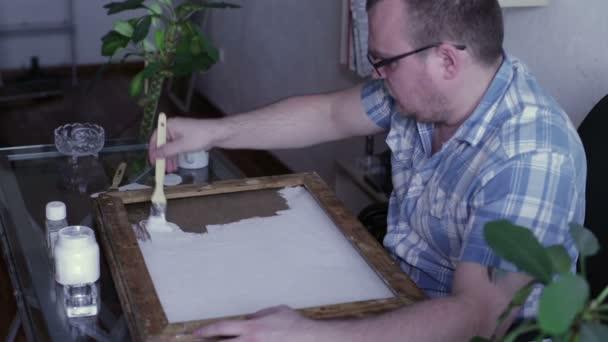 Muž pokrývá zem plátno