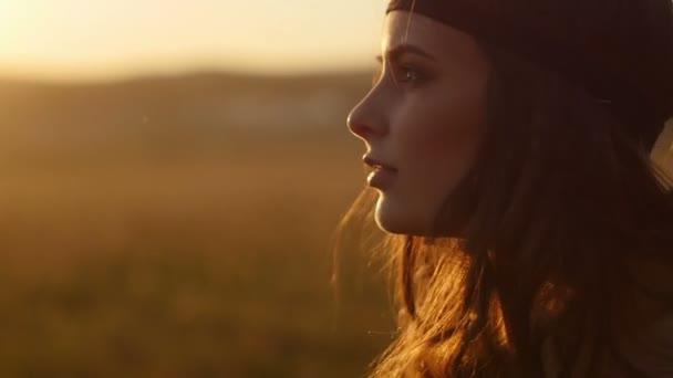 Dívka pózuje při západu slunce v oboru