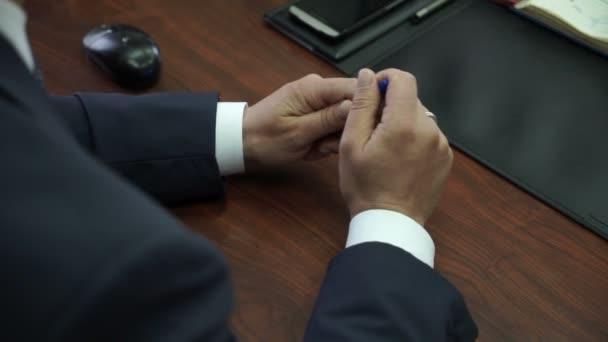 Člověk sedí v konferenční místnosti, nervózní, točil pero v ruce