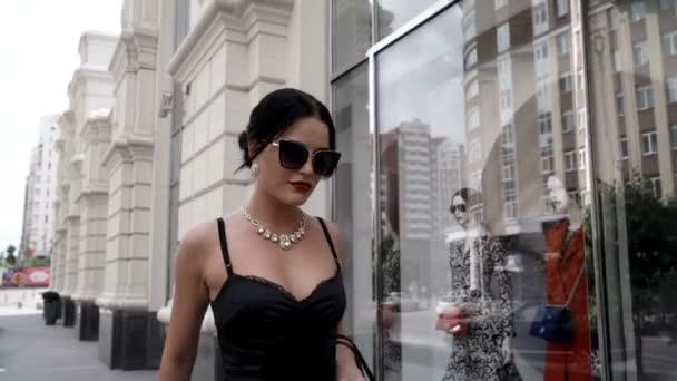 Elegantní a atraktivní dívka chodí městem podél obchodů