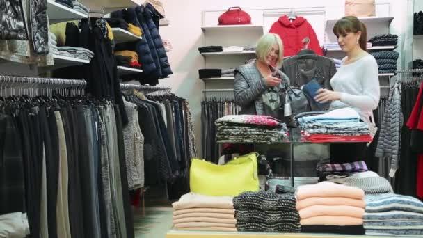 Holky v obchodě sledují oblečení a tašky