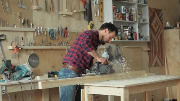 The man works with an electroplane in the carpentry workshop