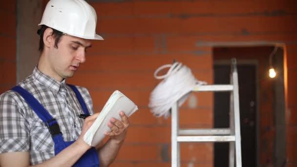 Tvůrce s Poznámkový blok na staveništi