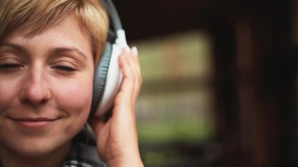 Girl in headphones listens to music closeup front