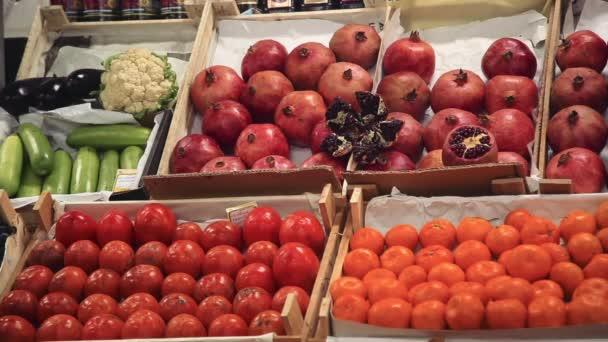 Granátová jablka, kaki a mandarinky na regály v obchodech