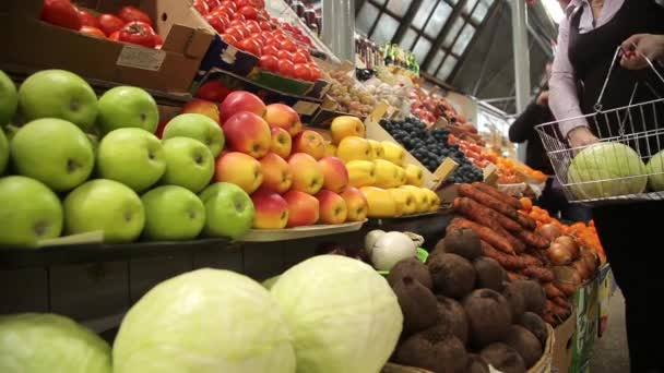 Žena nakupuje zeleninu na trhu statku
