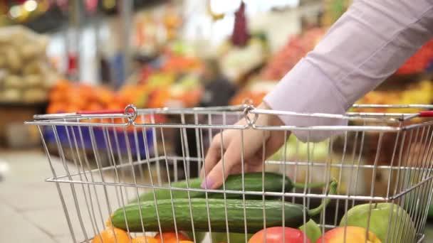 Nákupní košík se zeleninou na pozadí na trhu