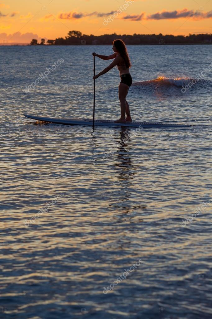 Woman stand up paddleboarding at sunrise