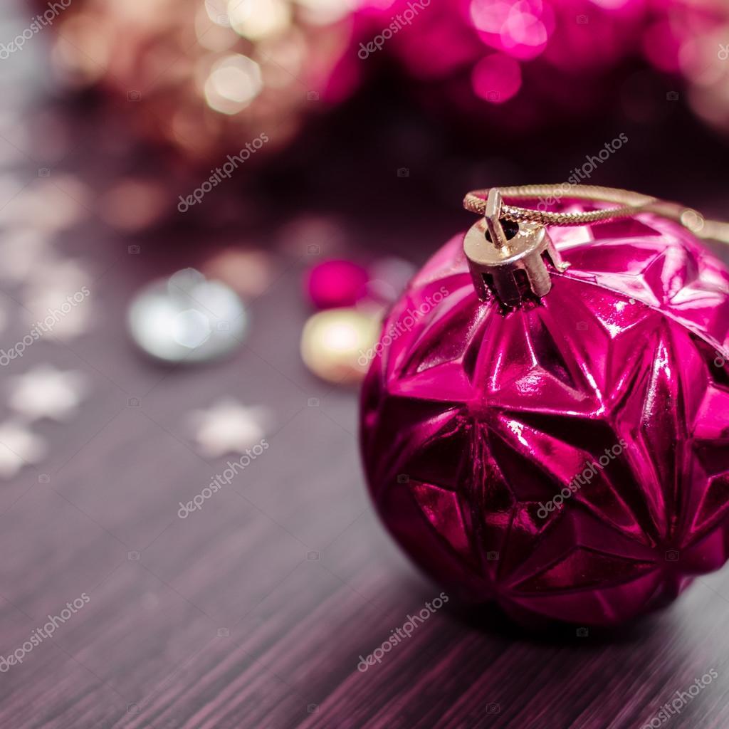 Magenta Christmas Ball On Bokeh Background Of Xmas Ornaments Stock Photo