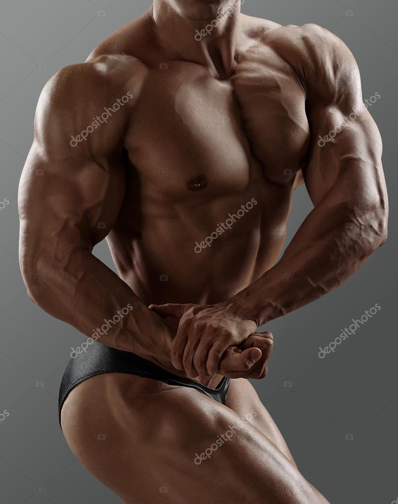 Gut aussehend Muskel Bodybuilder posiert auf grauem Hintergrund ...