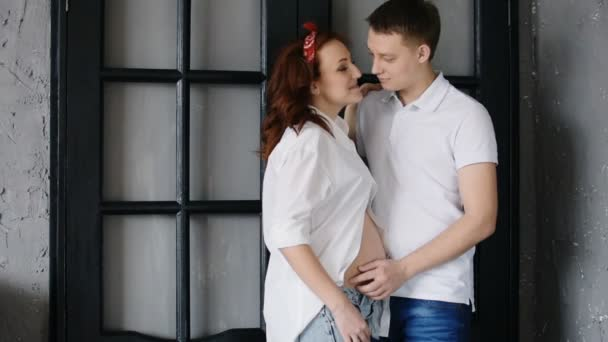 Beautiful young couple expecting a baby. Are standing in front of the doors in the house.