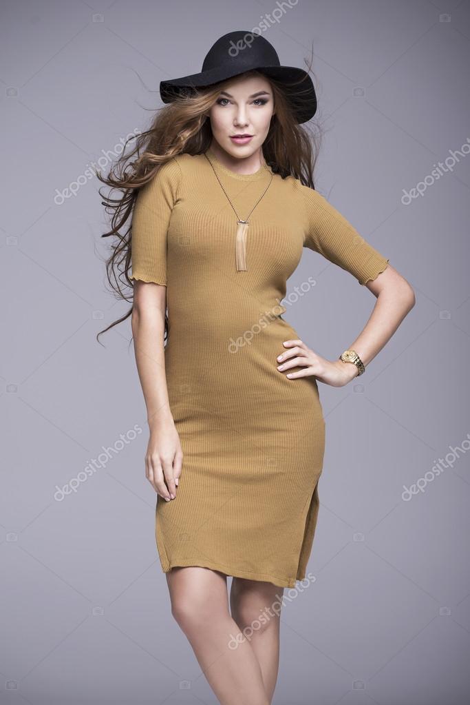 Bella donna con capelli lunghi in un vestito marrone e cappello nero–  immagine stock 114d5a9a4fff